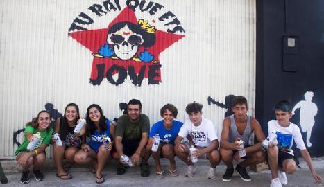 Alguns joves, amb l'artista Llukutter davant del mural.