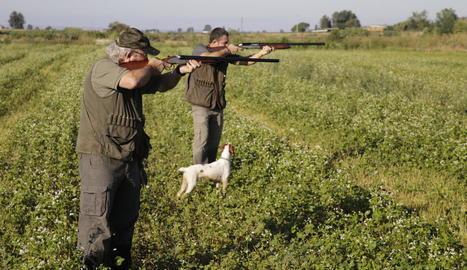 Imatge de dos caçadors ahir, el dia que va començar la mitja veda a Lleida.