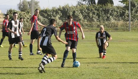Un jugador del Tàrrega controla la pilota davant d'un futbolista rival.
