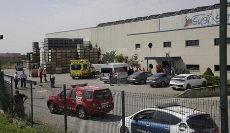 Serveis d'emergència i treballadors davant de l'empresa, situada a la carretera