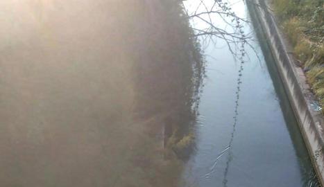 La grua amb el vehicle de les víctimes després de treure'l del canal a prop del lloc on van caure a l'aigua ahir a Bell-lloc.