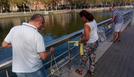 Diverses persones col·loquen llaços grocs als voltants del museu Guggenheim de Bilbao.