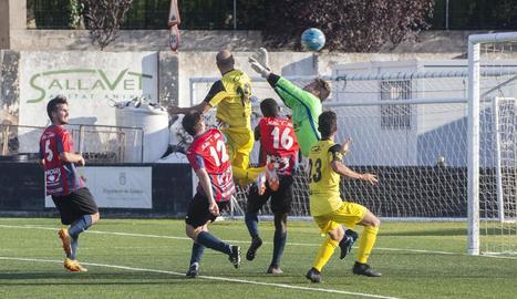 El visitant Adrià Fernández s'eleva per sobre de la defensa local per aconseguir el definitiu 1-1.
