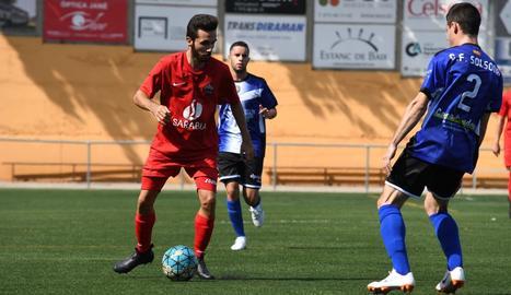 Un jugador de l'Alpicat controla la pilota davant de l'oposició d'un futbolista del Solsona, en una acció del partit d'ahir.