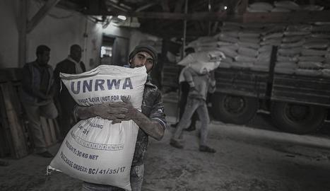 Un refugiat palestí porta un sac amb farina en un campament de refugiats de Gaza.