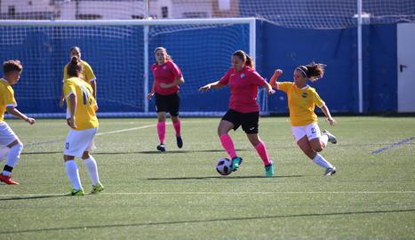 Una jugadora de l'AEM controla la pilota davant de la pressió d'una rival.