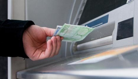 Un client treu diners d'un caixer automàtic.