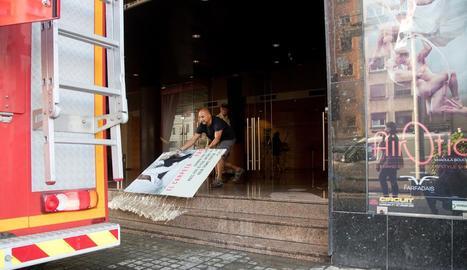 Un treballador del Teatre Victòria, al Paral·lel de Barcelona, traient aigua del recinte.