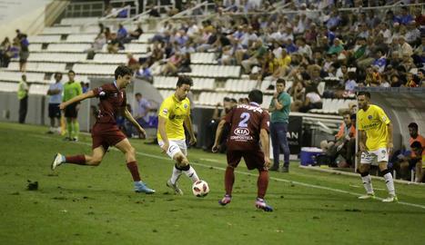 Pedro Martín intenta superar amb una passada la pressió de dos futbolistes del Compostel·la.