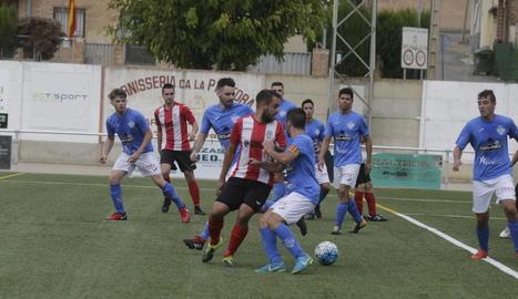 Un jugador del Puigvertenc intenta controlar la bimba entre la defensa de l'Alcarràs B.
