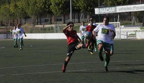 Un jugador del Coll controla la pilota davant de la pressió rival.