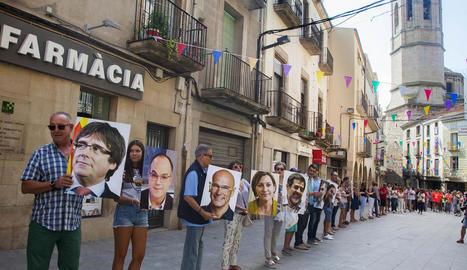 Participants en la cadena humana amb fotos de líders independentistes presos i a l'estranger.