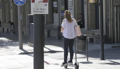 Una jove circula amb un patinet elèctric per rambla d'Aragó pel carril bici, ahir.