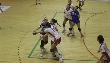 Una jugadora de l'Associació intenta avançar davant de dos rivals.