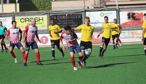 Un jugador del Balaguer i un altre del Lleida B lluiten per la possessió d'una pilota.