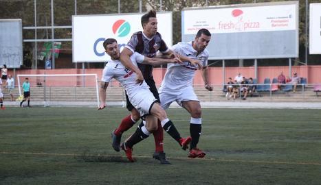 Dos jugadors del Borges intenten frenar l'avanç d'un rival del Júpiter.