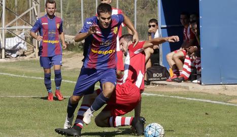 Un jugador de l'equip local avança amb la bimba tot superant l'entrada d'un rival.