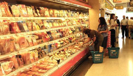 Imatge d'arxiu de clients fent la compra a la secció de carnis refrigerats.