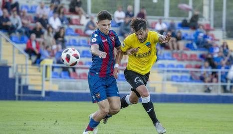 Joan Oriol intenta arribar a una pilota malgrat l'oposició d'un futbolista blaugrana.