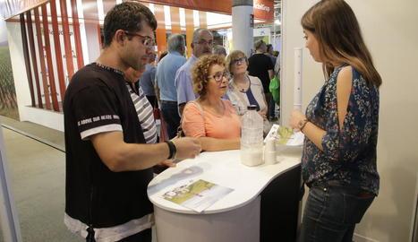 Visitants proven llet de cabra en un estand.