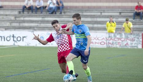 Un jugador del Balaguer i un altre de l'Igualada lluiten per la pilota.