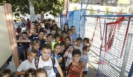 Pares i alumnes del Tonucci, al costat de la pista poliesportiva precintada.