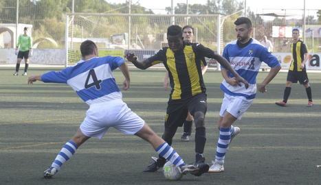 Un jugador de l'equip visitant intenta prendre la pilota a un del local.
