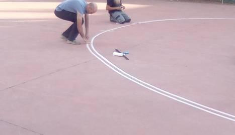 Un dels pares pinta la línia de l'àrea.