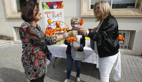 Una dona col·labora ahir amb la campanya 'Una flor per a un projecte 2018' de l'Oncolliga.