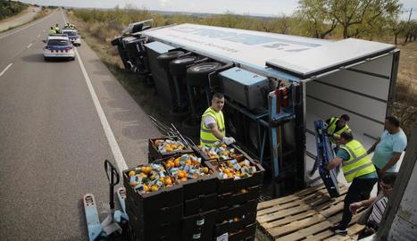 Les caixes de mandarines que portava el camió sinistrat es van carregar a un altre tràiler.