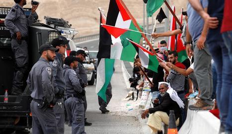 Soldats israelians davant civils palestins, ahir, a Cisjordània.