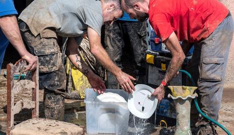 Voluntaris mallorquins donant un cop de mà en l'extracció de llot a la localitat afectada, ahir.