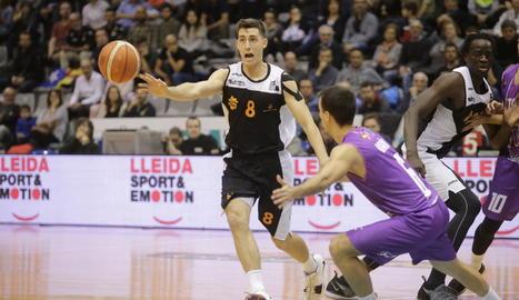 Adrián Chapela, un dels jugadors més destacats del Força Lleida, passa la pilota a un company davant la pressió de Javier Marín.