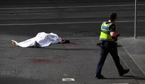 El cadàver de la víctima, a terra, custodiat per un policia.