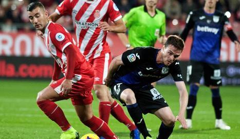 Borja García intenta emportar-se la pilota davant de la persecució d'Eraso, ahir a Montilivi.