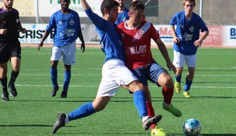 Un jugador de l'equip local i un del visitant es disputen per la pilota.