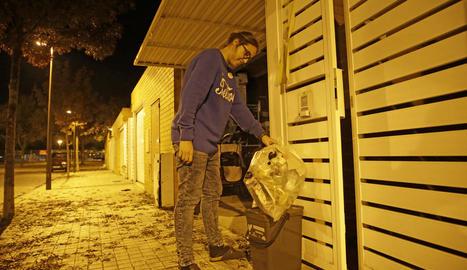 Una veïna treient les bosses d'escombraries ahir a la nit.