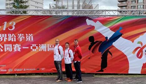 Els tres integrants de la selecció espanyola de taekwondo posen al costat d'un dels cartells que anuncien el Mundial a Taipei.