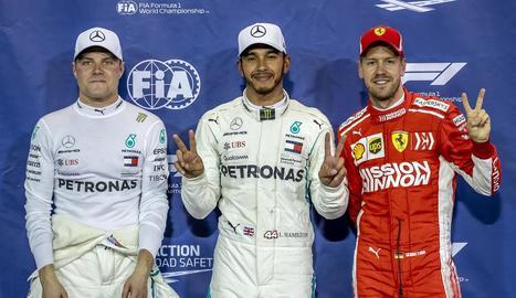Hamilton, flanquejat pel seu company Bottas i Sebastian Vettel.