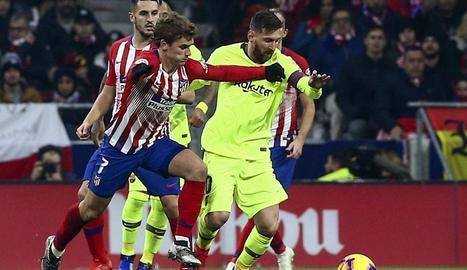 Leo Messi intenta avançar amb la pilota davant la pressió del francès Griezmann, en un partit en el qual cap dels dos va brillar especialment.