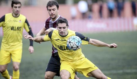 Un jugador del Balaguer defensa la pilota davant la pressió d'un jugador del Júpiter.