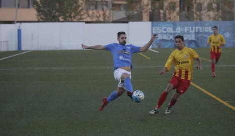 Un jugador de l'Alcarràs colpeja la pilota davant la pressió rival.