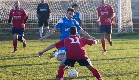 Un jugador de la Seu intenta desplaçar la bimba davant l'oposició d'un rival.