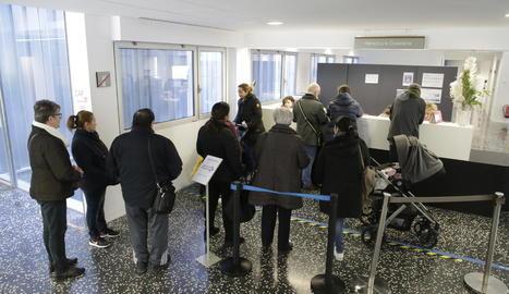 Pacients esperant davant del taulell de programació de visites en un CAP.