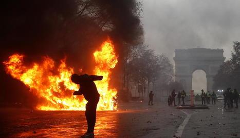 Un grup d''armilles grogues' ('gilets jaunes') s'enfronten a la policia antiavalots prop de l'Arc de Triomf a París.