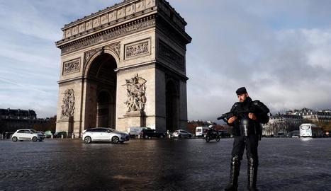 Un policia fa guàrdia davant l'Arc del Triomf, monument que va registrar danys durant els disturbis.