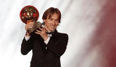 Luka Modric mostra el trofeu ahir a la nit a París.