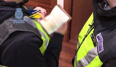 Agents revisant passaports durant l'operatiu policial.