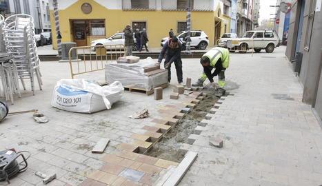 Un grup d'operaris repavimentaven el carrer del Riu, ahir.