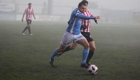 Un jugador del Binèfar disputa la pilota amb un rival durant el partit.